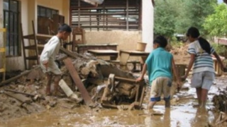 children trying to salvage their home after a flood